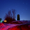 HAZEL ROAD<br /> This is a nine-minute exposure taken when the temperature on Hazel Road was 1 degree above zero. I decided to wait in the van. The tail lights caused the reddish snow. The green glow is a yard light near the farmhouse. Scattered light makes the sky appear blue, even at night, especially near the horizon.<br /> <br /> Date: January 9, 2010<br /> Exposure: 9 minutes<br /> Aperture: f/3.5<br /> ISO: 100<br /> Focal Length: 18mm<br /> (Click image to enlarge)