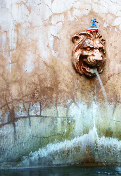 """Surfing the Lion""<br /> A small plastic toy rests atop a leonine fountain spigot.  Balboa Park, San Diego, California.  Image # BB02  Mini."