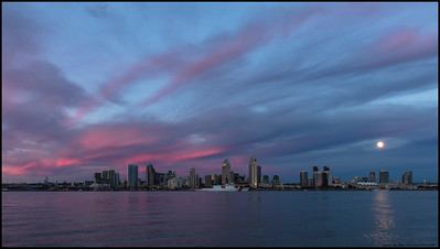 Reflected sunset colors over San Diego as the full moon rises in the East and a Coast Guard cutter passes in front of downtown.