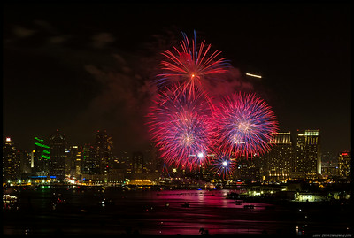 The fireworks over downtown San Diego last night.  Left the plane's light trail in so you can see the flights were still ongoing.  Another set of fireworks were going off to the east, behind the buildings to the left.