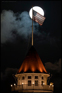 The Star Spangled Banner atop the ballroom tower of the Hotel Del Coronado while the moon rises.