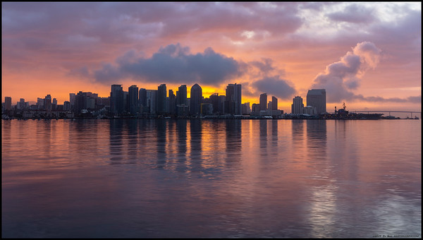 The clouds provided a nice diffusion filter to the sun rising behind the city.
