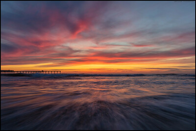 The red phase of the sunset over Ocean Beach as the waves rush shoreward.
