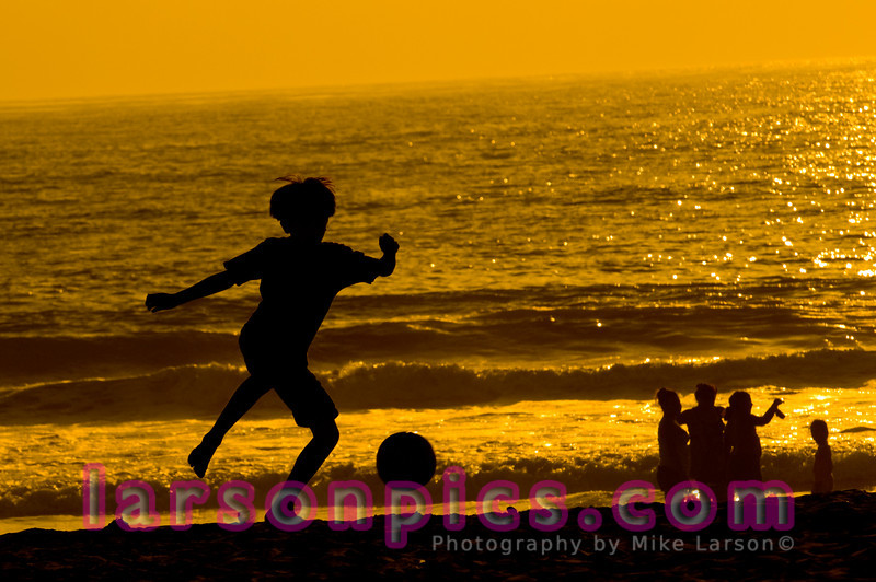 Boy Playing Soccer on Beach