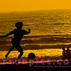 Boy Playing Soccer on Beach