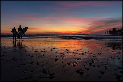 A pair of surfers waiting for friends who were determined to catch the final sunset wave.