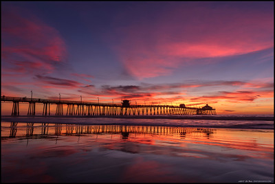 The Imperial Beach pier swathed in sunset colors at low tide.