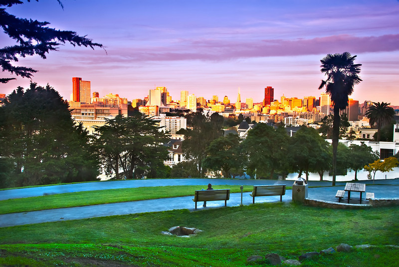 San Francisco at Dusk with a strong sunset over the city.  Golden lights and purple skies