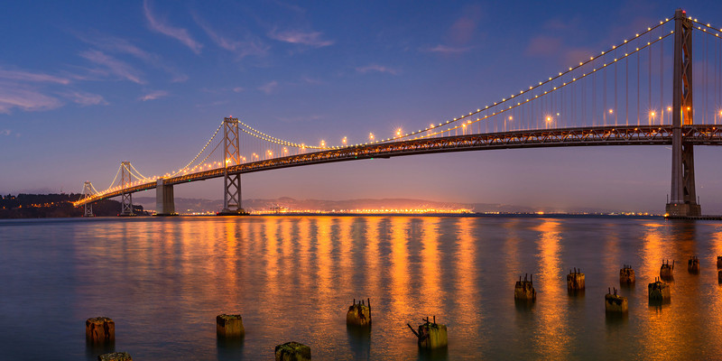 """San Francisco Bay Bridge at Dusk"" Nothing better than a nice warm glow of lights on the Bay Bridge and Oakland in the evening. I captured this on the waterfront with the pilings in the foreground while a guest on a friend of mines San Francisco photo workshop. I really enjoy helping teaching other people so I might have to look into doing this more! If you want some great locations to shoot from in the evening with other folks and good instruction, check out his workshops. Having a bus and driver makes zipping around the city pretty nice to shoot!  This Panorama is a 1:2 ratio panorama.  Print sizes can range from 20"" x 40"" , 24"" x 48"", 30"" x 60"" or larger.  This also can work as a triptych or multi-image layout."