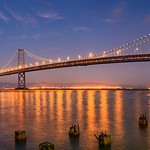 """""""San Francisco Bay Bridge at Dusk"""" Nothing better than a nice warm glow of lights on the Bay Bridge and Oakland in the evening. I captured this on the waterfront with the pilings in the foreground while a guest on a friends San Francisco photo workshop.  The San Francisco waterfront and Bay Bridge I never get tired of capturing."""