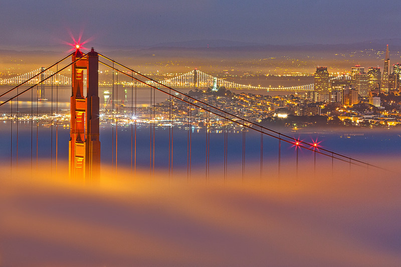 Low fog sits on the deck of the Golden gate bridge.  the city can be seen glowing in the distance.  it was a epic night of photographing one of the cities infrequent occurrences.