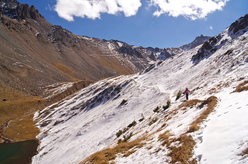 "A hiker traverses an icy slope to reach the ""upper"" Blue Lake beneath the west face of Mt. Sneffels; Colorado San Juan Mountains."