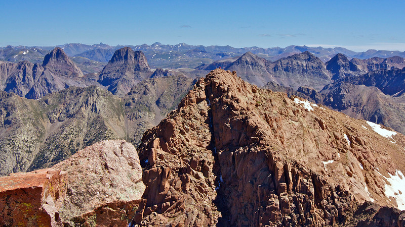 A hiker (in red) stands atop North Eolus, viewed from the summit of Mount Eolus; Colorado San Juan Range