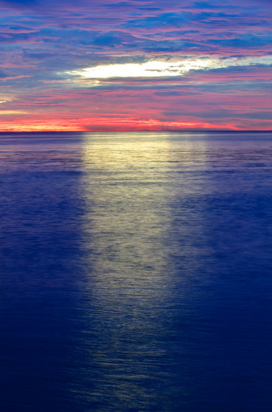 """""""Reaching Down at Sunset"""" This was the finalé of the sunset with an opening in the middle and """"God Beams"""" (those mysterious rays of light) coming down. Just a circle opening in the blues, pinks and purples of the sky."""