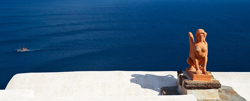 A statue by the blue Aegean sea.
