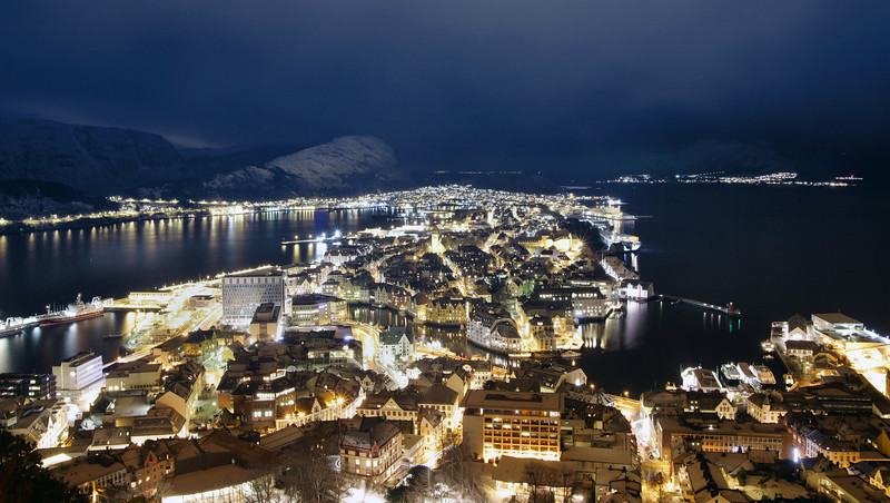 Panoramic aerial view of Alesund, Norway at night with snow capped mountains and traffic trails. Taken from mount Aksla.
