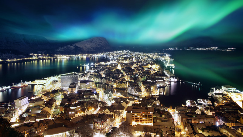 Panoramic aerial view of Alesund, Norway at night with snow capped mountains and Northern Lights (Aurora Borealis)