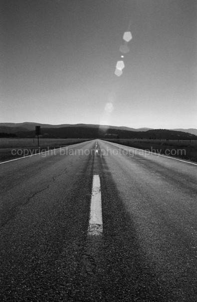 Straight ahead... but lookin behind on the road to Swan Lake, Rt.200 Montana. Greyscale