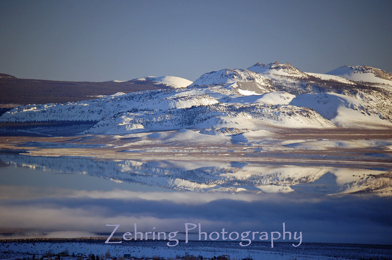 Perfect reflection of the Sierras on Mono Lake interrupted by a fog bank rolling through the foreground.