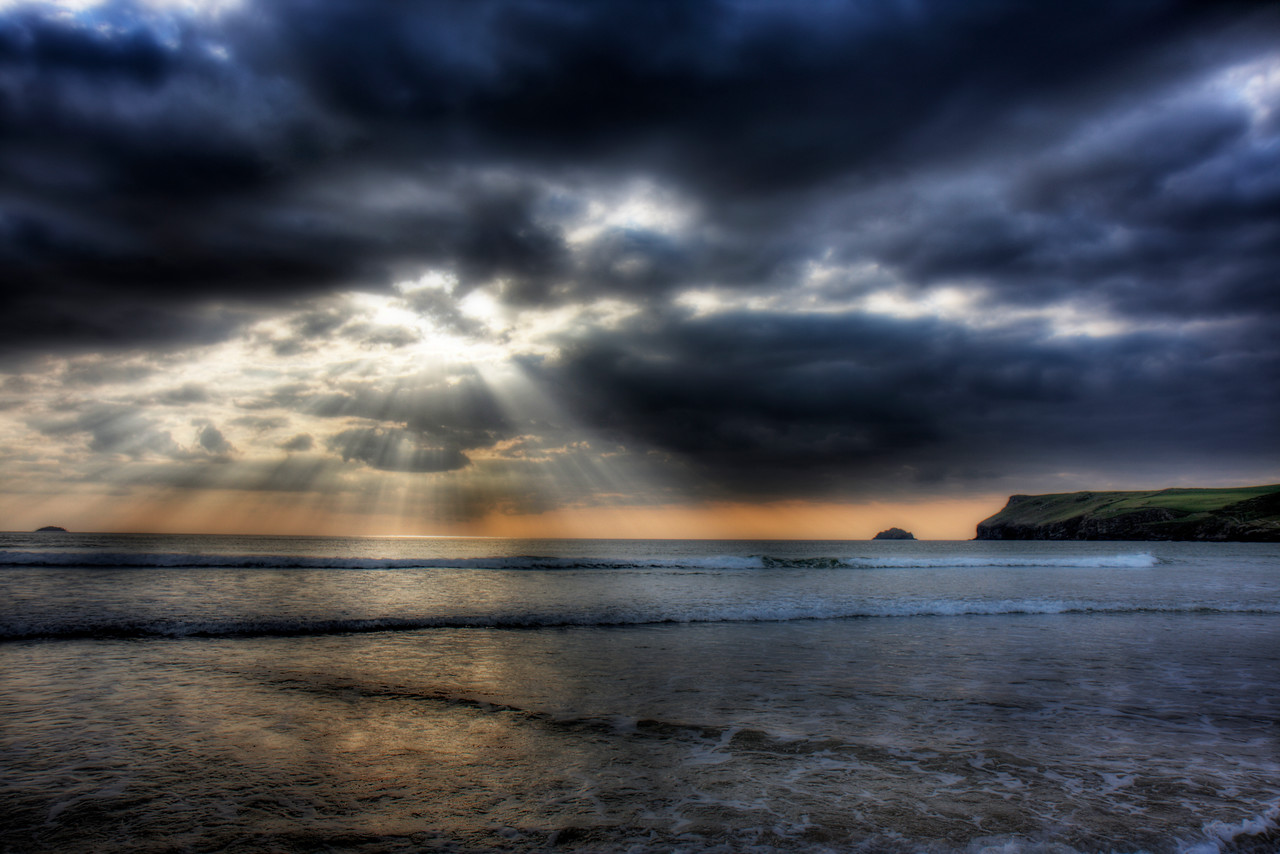 The long dark tea time of the soul  Atlantic ocean in spring. Rays of light bust through the clouds.