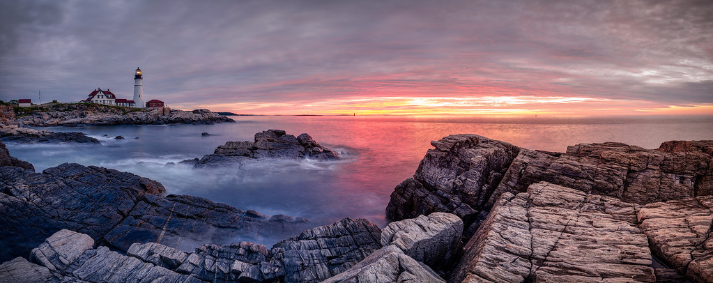 Pinks and yellows burst through a gray, cloudy sky during sunrise at 5:02 AM on July 26, 2012 at Portland Headlight in Fort Williams Park in Cape Elizabeth, Maine.  This image comprises multiple photos stitched and blended together to form an ultra-high-resolution, high dynamic range panorama that is over 105 megapixels.