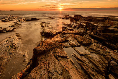 Golden sunrise illuminates a rocky outcrop near Two Lights State Park in Cape Elizabeth, Maine.