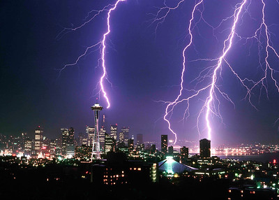 """""""Lightning Strikes Thrice"""" A very rare, Great Plains-like lightning storm of historic proportions over Seattle in July of 1984 which did significant damage to many power poles and transformers around town. This shot was one of one hundred taken during the storm and probably at its peak. The bolts are sequential from right to left and show how the cloud recharged itself over time...the first strike on the right is a bruiser, the second rather weak. The heavy bolt on the left actually hit a utility crane which was positioned atop the Columbia Center building and knocked out its wiring. How do I know? The crane operator happened by the Market some time later and told about me about showing up to work and finding his crane """"fried""""."""