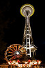 Space Needle from the base at night with ferris wheel and carousel