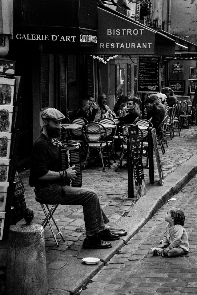 A child listens to an accordian player in Montemartre, Paris.