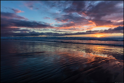The tide was coming in as the sun set, making it challenging to catch the brief colors. between the waves.