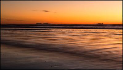 The Coronado Islands rise above the low tide wavetops.