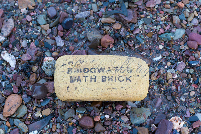 An old Bridgwater Bath brick on the beach at Doniford Bay in Somerset after high tide during heavy storms.