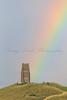 Rainbow after heavy rain behind St Michael's Tower on Glastonbury Tor