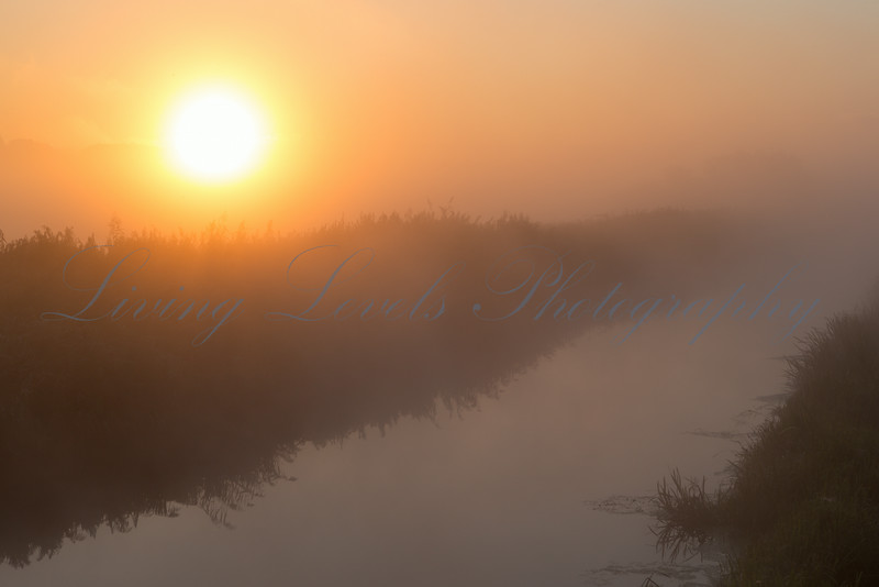 Sunrise over the River Brue on a misty September morning.  This viewpoint is from the road bridge known as cowbridge