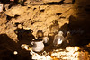 A collecton of old bottles and cauldrons is lit in a side chamber at Wookey Hole Caves