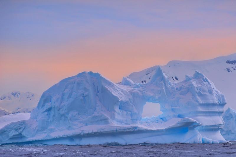 Giant Iceberg With Hole At Sunset
