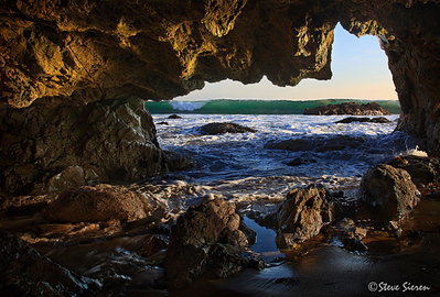 Santa Monica Mountain Sea Cave  Shot this one while leading one of my California Coastal workshops last week.  I crouched for quite some time here timing the waves for one that had enough height to crash over the distance rocks to convey a feeling of how this seacave was sculpted.   Southern California near Los Angeles