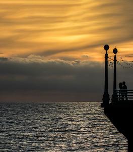 A couple embraces, sunset Manhattan Beach Pier.