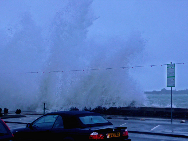 Car drivers try to make their way into work on the main road that runs parallel to the sea wall...