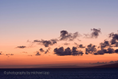 "Sunset off coast of Maui, near Kaanapali.  The deep orange color is due to ""vog"" - volcanic fog from a newly opened vent on the big island."