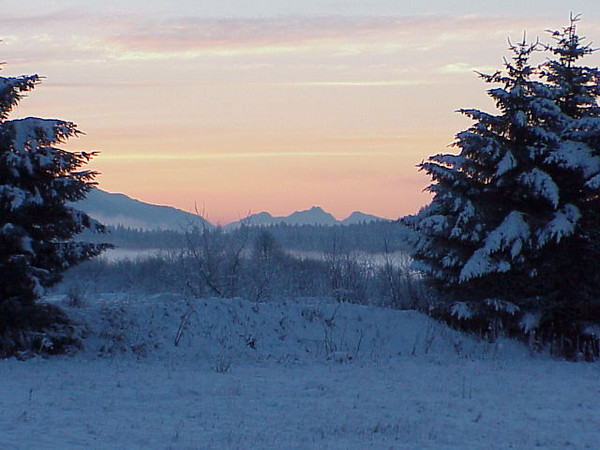 Midwinter sunrise looking south across snowy fields toward Juneau, Alaska.
