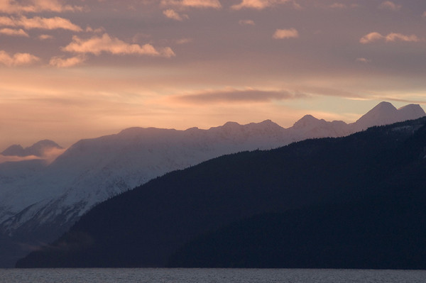 The rising sun casts an orange glow in the southern sky along Turnagin Arm south of Anchorage, Alaska during late autumn.