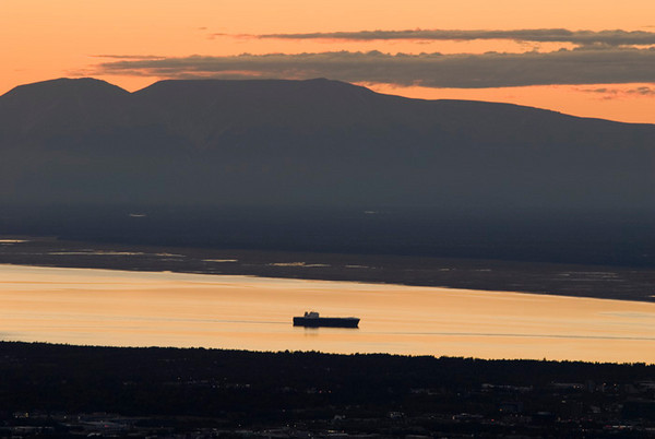 This cargo ship was arriving in Anchorage via Cook Inlet just at sunet. This photo was taken from the overlook at Glen Alps in the Chugach State Park just outside Anchorage, Alaska in early September. The mountain in the background is Mount Susitna, also known as Sleeping Lady.