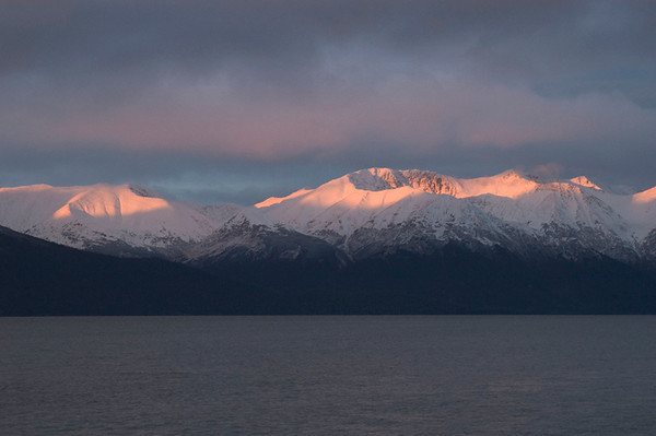 Sunrise along Turnagin Arm south of Anchorage, Alaska lights up the top of the snow on these peaks during late autumn.