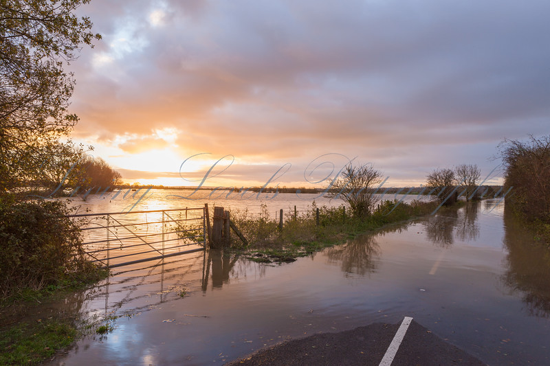 Dawn over the flooded Glastonbury to Street road after the River Brue burst its banks
