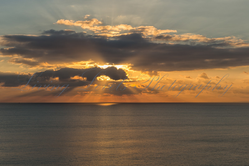 The suns sets over the calm English Channel near Burton Bradstock, on an early winter's day.