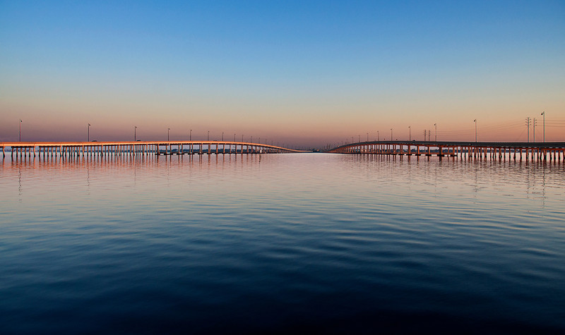 The Tamiami Trail splits as it enters Punta Gorda from the south to run on two parallel one-way city streets. The north- and southbound lanes funnel onto two separate bridges over the Peace River between Charlotte Harbor and Punta Gorda seen here at sunrise in late April, 2012.<br /> <br /> (There is a way-cool Tiki Bar behind the Sheraton that is right between the two. It was not open at sunrise.)