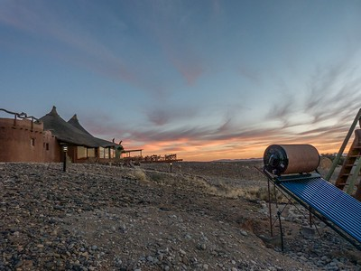 A view of the beautiful sunset and the main lodge building.  Notice the solar hot water tank in the lower right.