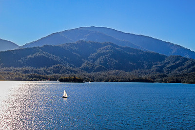 A sailboat enjoys a quiet afternoon on Whiskeytown Lake with Shasta Bally (elevation 6,000 feet) looming in the distance.