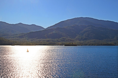 A lonesome sailboat plies the afternoon waters of Whiskeytown Lake with Shasta Bally (elevation 6,000 feet) looming in the distance.